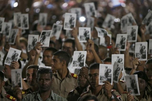 Lãnh tụ Fidel Castro đã đưa đất nước Cuba từng bước phát triển, tập trung vào các chính sách về y tế và giáo dục miễn phí cho người dân. Trong ảnh: Những người lính Cuba cầm trên tay bức ảnh chụp lãnh tụ Fidel Castro thời trẻ trong lễ tưởng niệm.