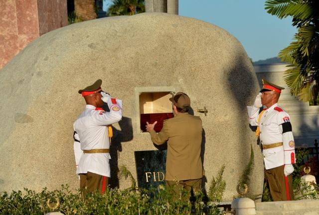Chủ tịch Cuba Raul Castro đã đặt quan tài gỗ đựng tro cốt của lãnh tụ Fidel Castro vào bên trong ngôi mộ bằng đá tại nghĩa trang Santa Ifigenia hôm 4/12 (Ảnh: Reuters)