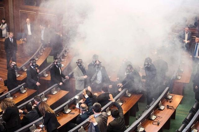 Cảnh sát Kosovo đeo mặt nạ chống độc tiến vào kiểm tra tòa nhà quốc hội sau khi các nghị sĩ phe đối lập phóng bom khói tại quốc họp quốc hội ngày 19/2 ở Pristina. (Ảnh: Getty)