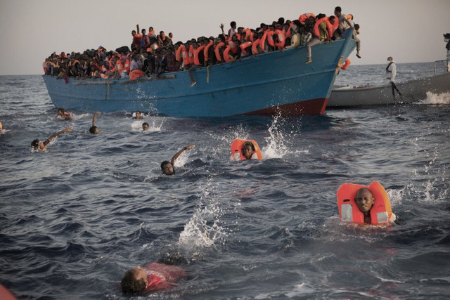 Những người di cư nhảy từ trên một thuyền gỗ chật cứng người xuống biển khi họ được giải cứu ở bờ biển Libya ngày 29/8. Hàng chục nghìn người đã thiệt mạng khi cố vượt qua vùng biển ở Địa Trung Hải để đến được châu Âu (Ảnh: AP)