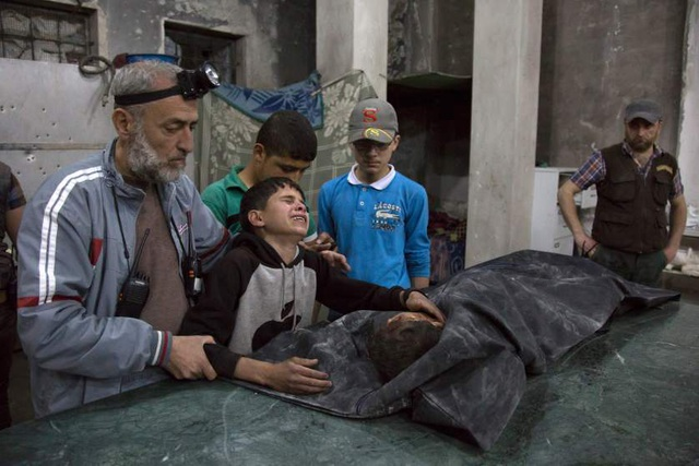 """Cậu bé người Syria khóc nức nở bên thi thể người thân bị thiệt mạng trong một trận không kích tại """"chảo lửa"""" Aleppo hôm 27/4 (Ảnh: Getty)"""