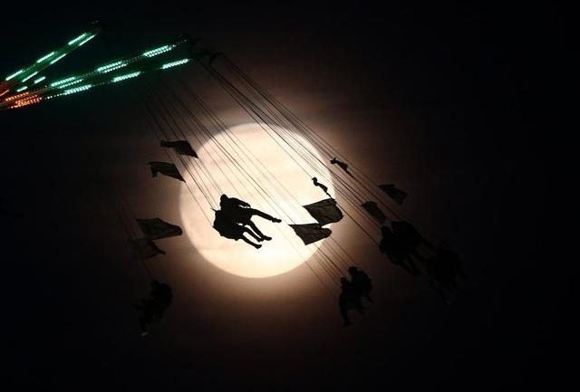 """Bóng người chơi đu quay ở công viên giải trí tại thủ đô London, Anh hôm 13/11 in trên nền trời trong khoảnh khắc """"siêu trăng"""" hiếm có. (Ảnh: Reuters)"""