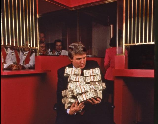 """Bức ảnh do phóng viên ảnh Harry Benson chụp ông Trump ở Atlantic City cho báo People vào năm 1990. """"Ngay sau khi sòng bạc Taj Mahal khai trương ở Atlantic City vào năm 1990, tôi đã đến đó để chụp ảnh Donald Trump. Ông ấy nói với tôi rằng có hơn một triệu USD tiền mặt trong két của sòng bạc. Tôi nói với ông ấy rằng tôi chưa được thấy một triệu USD tiền mặt bao giờ. Và thế là ông Trump đi thẳng vào két, lấy ra đúng một triệu USD, ôm vào người để chụp ảnh. Hành động này của ông Trump vào thời điểm đó gây hoang mang cho nhiều người vì theo luật của sòng bạc, không ai được phép mang tiền mặt ra ngoài. Tôi thấy đây là bức ảnh đáng nhớ nhất trong ngày hôm đó"""", Harry Benson kể lại."""