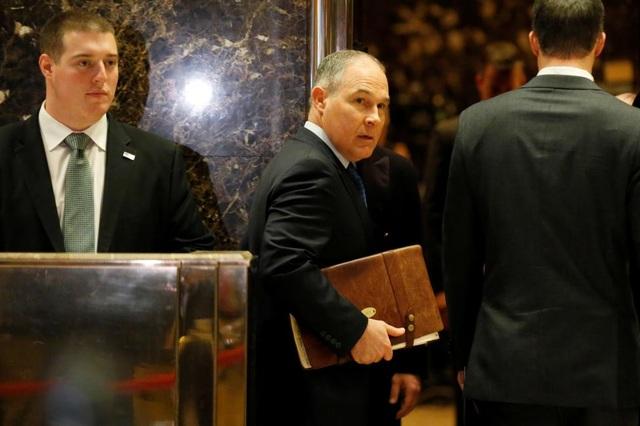 Ông Scott Pruitt (giữa) - tổng chưởng lý của bang Oklahoma - đang chuẩn bị bước vào thang máy tại tháp Trump. Tổng thống đắc cử Trump đã chọn ông Pruitt, người từng phản đối chính sách chống biến đổi khí hậu, vào vị trí lãnh đạo Cơ quan bảo vệ môi trường (EPA) trong nội các mới.