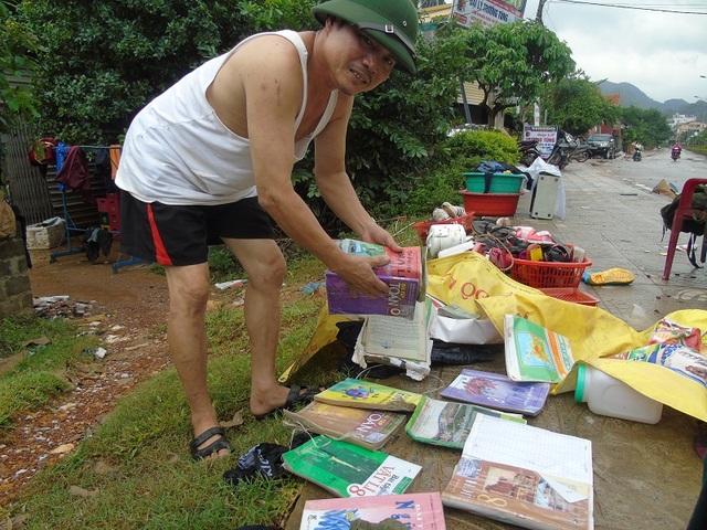 Anh Hồ Tứ tại xã Sơn Trạch đang lau dọn, phơi những cuốn sách bị ướt cho đứa con đang học lớp 8