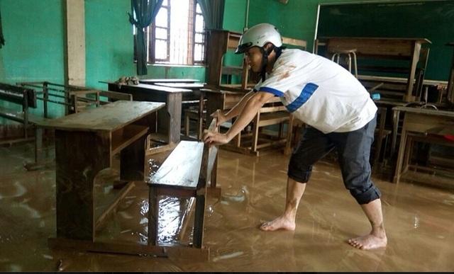 Các giáo viên và học sinh Trường THCS Văn Hoá lau chùi bàn ghế và phòng học sau lũ