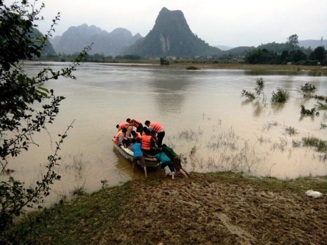 PV Dân trí chuẩn bị lên ca nô vượt dòng sông dữ để tiến vào vùng rốn lũ Tân Hoá (Ảnh: Tiến Thành)