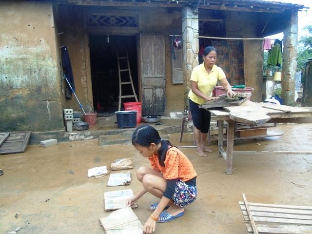 Hai mẹ con chị Hoàng Thị Văn đang cố nhặt những gì còn sót lại sau lũ.
