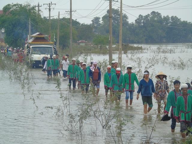 Dòng người lội nước đưa tiễn nữ sinh lớp 12 về nơi an nghỉ khi con đường vào thôn Vinh Quang vẫn đang chìm trong nước lũ.