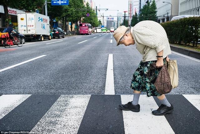 Bà cụ này lưng đã còng tới mức gần như gập đôi, nhưng bà vẫn chủ động trong các sinh hoạt thường nhật của mình, việc gì tự làm được, bà vẫn tự làm. Trong ảnh, bà vẫn đi bộ nhanh thoăn thoắt sang đường ở quận Shinjuku, Tokyo.