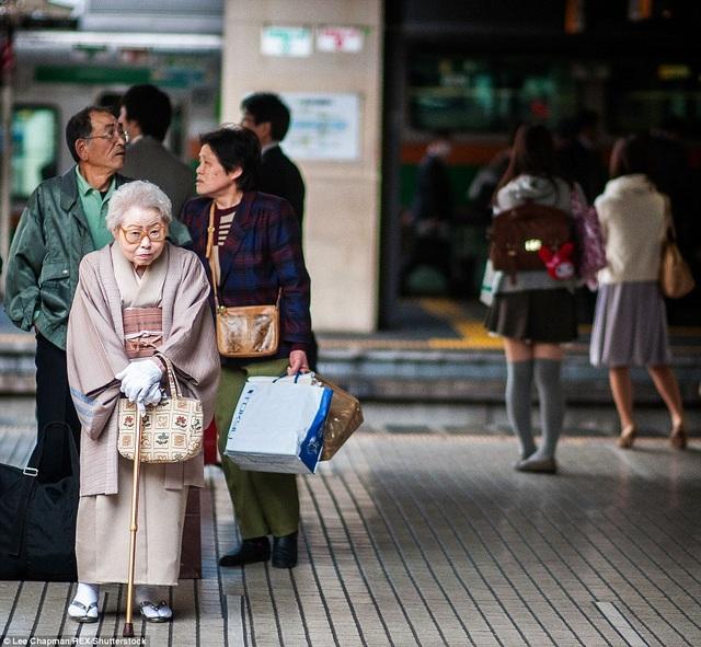 Một bà cụ đang đứng chờ tàu ở nhà ga thuộc khu trung tâm Tokyo.