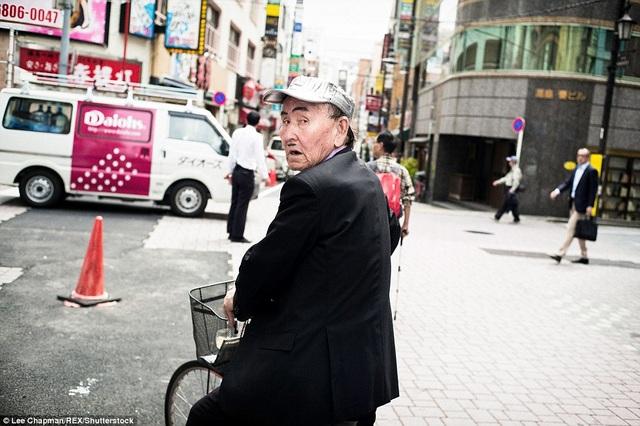 Một ông cụ người Nhật đang đạp xe trên đường. Ông cụ đã dùng bút tự tô đậm thêm lông mày và vẽ thêm một đường ria mép, có thể thấy ông là người khá hài hước với tuổi tác.