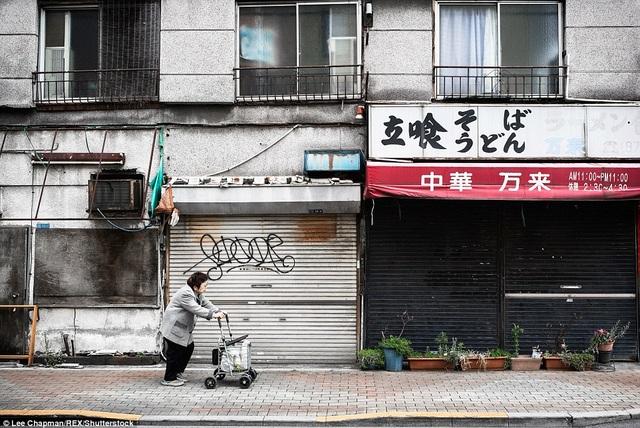Một bà cụ đang đẩy chiếc xe đi chợ của mình trên một vỉa hè ở khu dân cư nghèo của Tokyo.