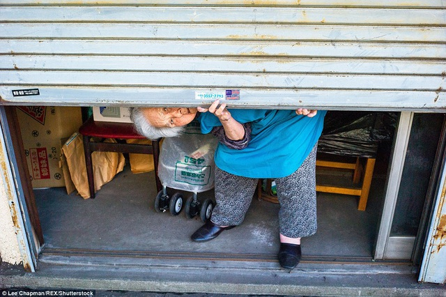 Bà cụ đang chuẩn bị mở cửa hàng lúc đầu ngày.