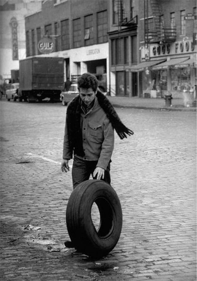 """1963: Kể từ sau album đầu tay, với sức sáng tạo nghệ thuật dồi dào và một sức bật đã được """"vào số"""", Bob Dylan bắt đầu cho ra hàng loạt album thu hút sự quan tâm chú ý của người yêu nhạc, đặc biệt là giới trẻ Mỹ. Bob Dylan bắt đầu trở thành một hiện tượng. Trong bức ảnh được chụp bởi nhiếp ảnh gia Jim Marshall - một tay máy chuyên chụp hình các ngôi sao, cá tính Bob Dylan được khắc họa đầy thú vị. Bob Dylan dù là một biểu tượng âm nhạc nhưng không bao giờ mang phong cách của một ngôi sao. Từ trước đến nay, ông luôn theo đuổi một cá tính chân thực cả trong âm nhạc và đời sống. Khoảnh khắc này đã chụp lại một ngôi sao ca nhạc đang trên đường đi ăn sáng, tình cờ bắt gặp một chiếc lốp xe cũ, người thanh niên ấy liền thích thú chơi đùa. Cũng trong năm này, Bob Dylan cho ra mắt album thứ hai - """"The Freewheelin Bob Dylan"""" (1963)."""