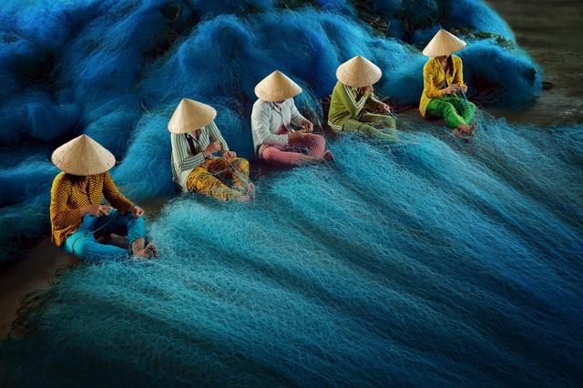 """Ở hạng mục """"Travel"""" (Ảnh du lịch), bức ảnh đoạt giải khuyến khích do nhiếp ảnh gia người Việt - Lý Hoàng Long - thực hiện, được chụp ở Bạc Liêu, ghi lại cảnh những người phụ nữ đang khâu lưới đánh cá tại một làng chài."""