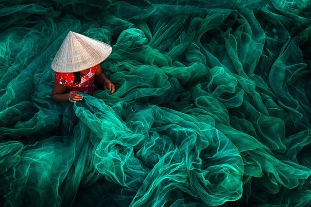 """Ở hạng mục """"Open Color"""" (Sắc màu mở), tác phẩm của Danny Yen Sin Wong (Malaysia) đã đoạt giải nhất. Tác phẩm được chụp tại một làng chài ở Phan Rang, ghi lại hình ảnh một người phụ nữ đội nón lá đang ngồi đan lưới đánh cá."""