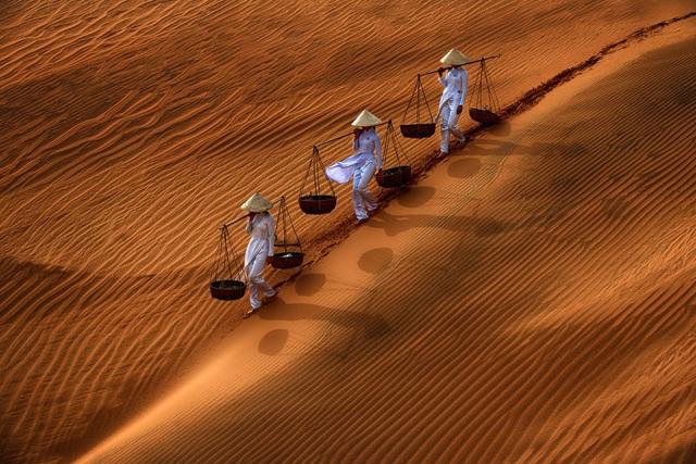 """Cũng ở hạng mục """"Open Color"""", giải khuyến khích tiếp tục là một khoảnh khắc đậm chất Việt và cũng do nhiếp ảnh gia Danny Yen Sin Wong (Malaysia) thực hiện. Ảnh chụp những đồi cát ở Mũi Né, với ba cô gái đang đi dọc một sườn đồi, họ mặc áo dài trắng và đội nón lá trong khi đang """"quang gánh trên vai""""."""