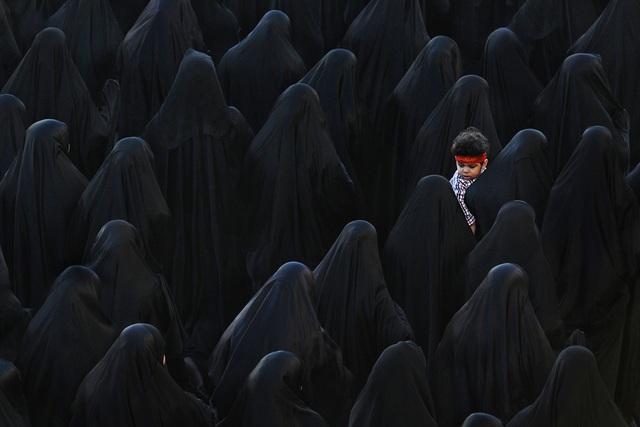 Đoạt giải ba là tác phẩm của tay máy Isa Ebrahim (Bahrain). Ảnh chụp một người phụ nữ đạo Hồi ở Bahrain đang bế trên tay cậu con trai nhỏ khi tham dự một lễ tang.