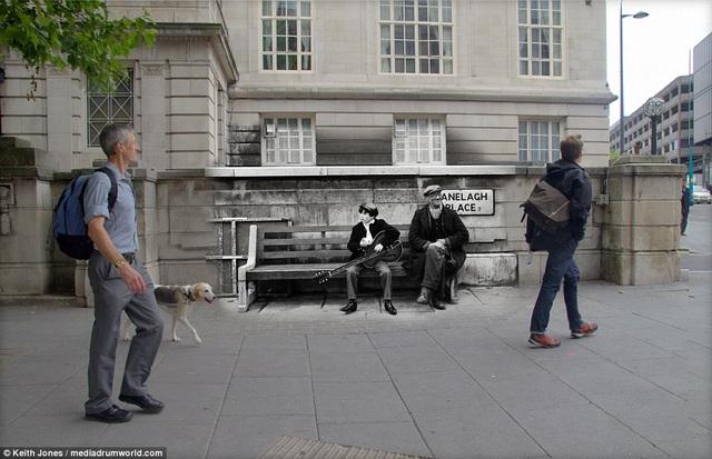 """Thuở ấy, hình ảnh những chàng trai ôm đàn ghita xuất hiện rất nhiều trên đường phố Liverpool. Trong ảnh là một cậu thiếu niên cũng """"học theo"""" phong cách của The Beatles, ôm đàn ngồi gảy trên đường phố."""