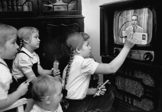 """Một cô bé đang tập trung vẽ lên màn hình TV, em không hề nghịch ngợm mà đang thực hiện theo đúng yêu cầu của chương trình - một chương trình tương tác với khản giả thuộc dạng sơ khai ở thời kỳ đầu của nền công nghiệp truyền hình. Đó là một chương trình dành cho thiếu nhi, có tên """"Winky Dink"""", lên sóng tại Mỹ trong 4 năm hồi thập niên 1950. Những đứa trẻ sẽ gắn lên màn hình một tờ phim trong và sẽ vẽ theo những chuyển động xuất hiện trên màn hình. Ảnh chụp năm 1953."""