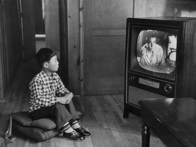 Cậu bé gốc Hàn Kang Koo Ri đang ngồi xem TV trong gia đình bố mẹ nuôi ở Los Angeles. Ảnh chụp năm 1956.