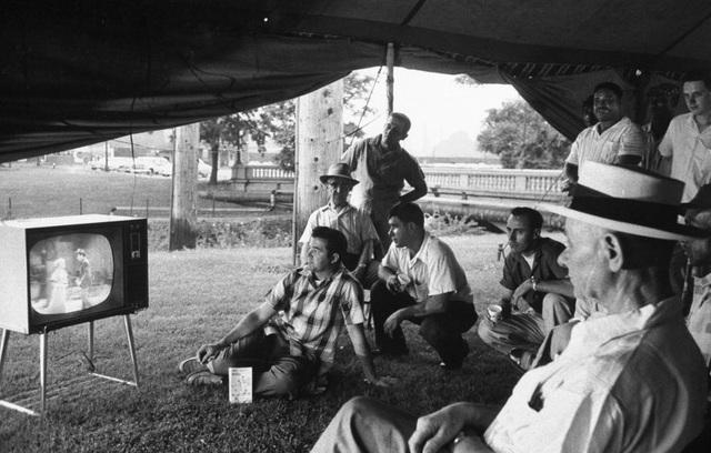 Những nông dân đang trong vụ thu hoạch nông sản cùng ngồi xem TV trong chiếc lều dựng lên bên rìa một nông trại ở thành phố Gary, bang Indiana, Mỹ. Ảnh chụp năm 1959.