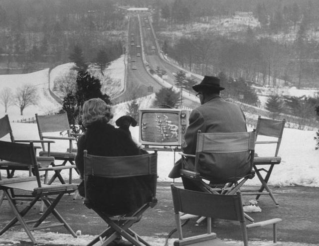 Một cặp vợ chồng theo dõi trận đấu bóng chày từ chiếc TV đặt bên ngoài một khách sạn nhỏ. Ảnh chụp hồi năm 1962.