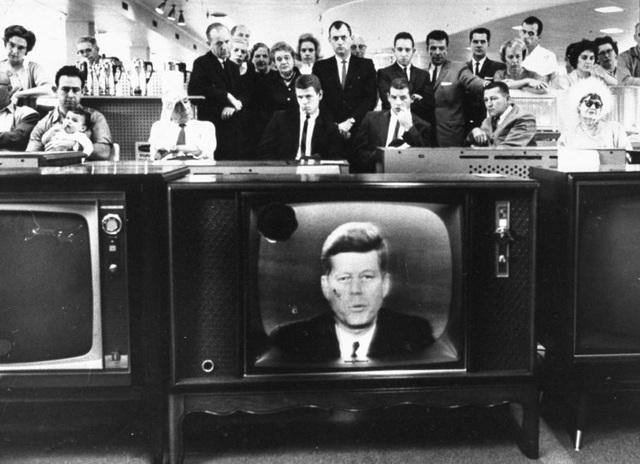 Đám đông theo dõi bài phát biểu của Tổng thống Mỹ John F. Kennedy qua truyền hình. Ảnh chụp hồi năm 1962.