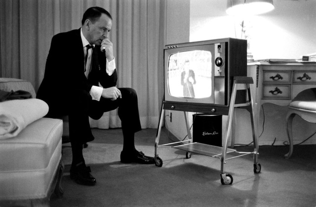 Nam ca sĩ Frank Sinatra theo dõi con trai của ông - Frank Jr. - khi đó 21 tuổi làm MC cho một chương trình truyền hình. Ảnh chụp năm 1964.