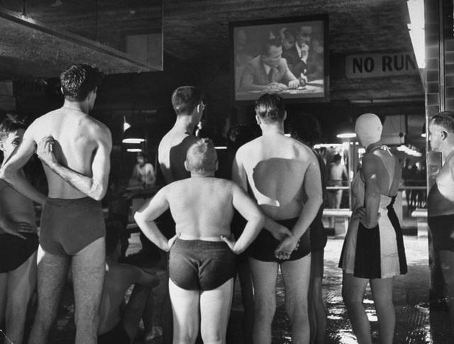 Những người đi bơi tại một bể bơi công cộng chăm chú theo dõi một bản tin thời sự. Ảnh chụp năm 1950.