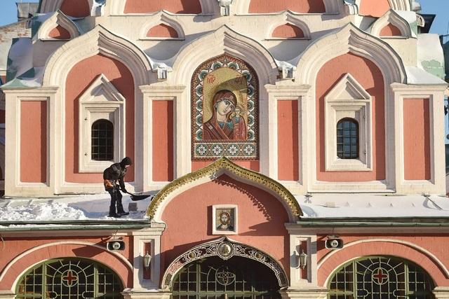 Một người đàn ông đang xúc tuyết khỏi mái của một nhà thờ nằm trên quảng trường Đỏ ở Moscow, Nga. Thời điểm này nhiệt độ có lúc xuống tới -13 độ C.