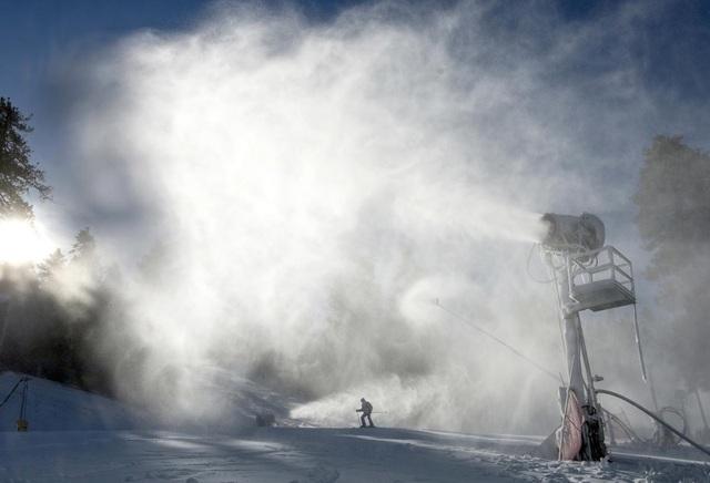 Một người trượt tuyết băng ngang qua một máy thổi tuyết ở núi High, bang California, Mỹ.