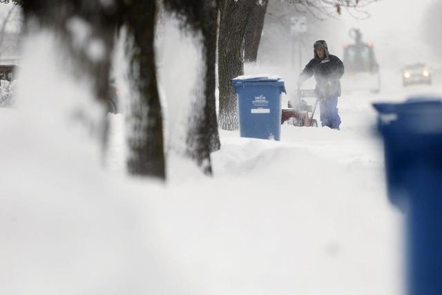 Những người công nhân dọn tuyết đang làm việc sau hai ngày tuyết rơi dày ở thành phố Winnipeg, Canada.