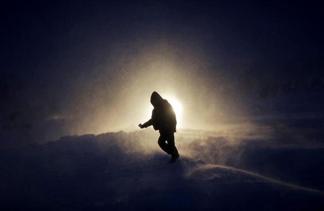 Một người bước đi trong cơn bão tuyết ở bang Bắc Dakota, Mỹ.
