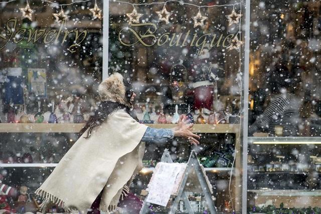 Người phụ nữ chơi trò ném tuyết bên ngoài một cửa hiệu nằm trong khu trung tâm thành phố Centralia, bang Washington, Mỹ.