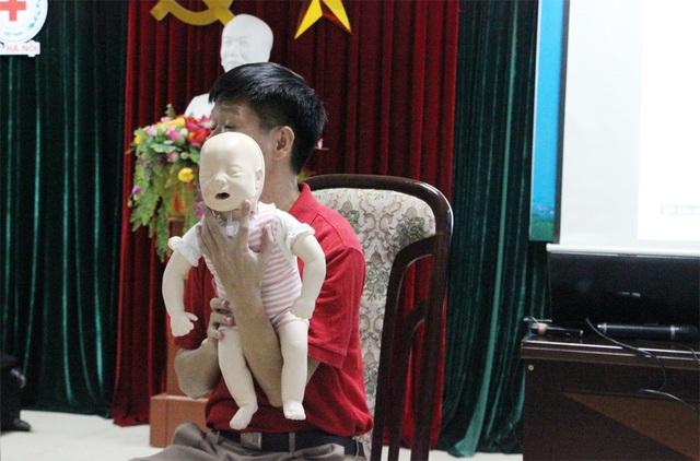 Dùng 2 ngón tay đỡ cằm em bé lên, mục đích đẩy cổ ngửa lên để dễ thở.