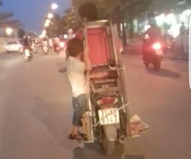 Hình ảnh bé trai đánh đu trên chiếc xe máy đang lao vun vút trên đường (Ảnh cắt từ clip).