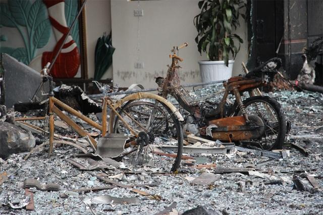 Nhiều xe máy, xe đạp, đồ đạc phía trước các ngôi nhà cháy bị thiêu rụi.