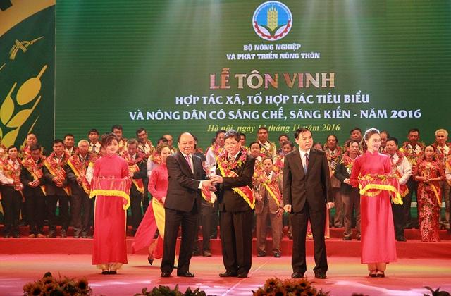 Thủ tướng Nguyễn Xuân Phúc và Bộ trưởng Bộ NN&PTNT Nguyễn Xuân Cường trao hoa và biểu tượng cho Hợp tác xã, tổ hợp tác tiêu biểu năm 2016.