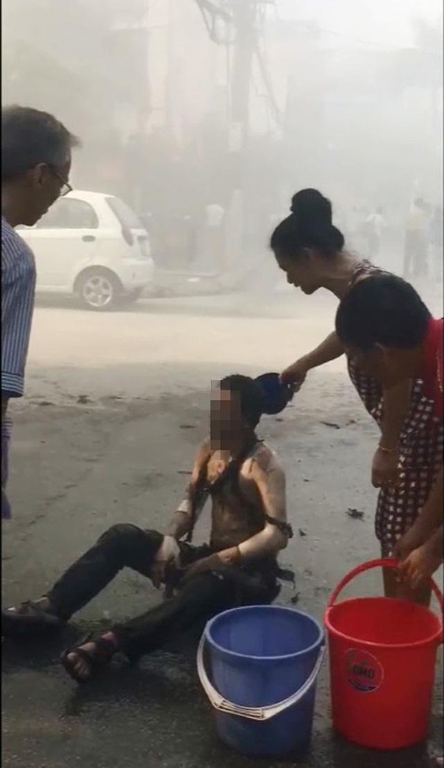 Hình ảnh người đàn ông bị bỏng được người dân dội nước lên người (Ảnh cắt từ clip).