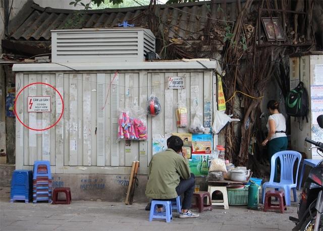 Mặc dù có biển cảnh báo nguy hiểm, không được lại gần ( ở vòng tròn đỏ) tại bốt điện này, nhưng người bán hàng nước và vị khách này vẫn ngồi sát (Ảnh chụp tại vỉa hè phố Vũ Tông Phan).
