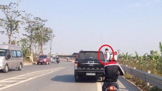 Nam thanh niên liều mình bám vào bên hông xe ô tô bán tải đang lao vun vút trên đường (Ảnh cắt từ clip).