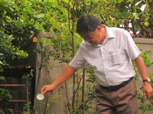 PGS.TS Bùi Văn Liêm rải rượu tại hố thám sát ở chùa Vạn Phước