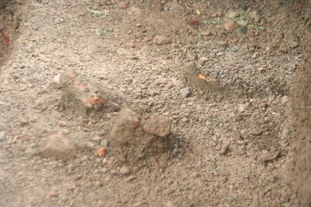 Một nền đất có một số hiện vật như gạch, vật dụng đất nung