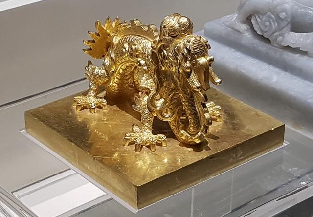 """Ấn """"Quốc gia tín bảo"""" bằng vàng thời vua Gia Long (1802-1819) dùng cho các văn kiện triệu tập các tướng lĩnh, phát động binh sĩ, trưng binh nhập ngũ và các văn kiện hành chính quan trọng. Ấn có cạnh 11,7x11,7cm, cao 9cm, dày 1,65cm."""