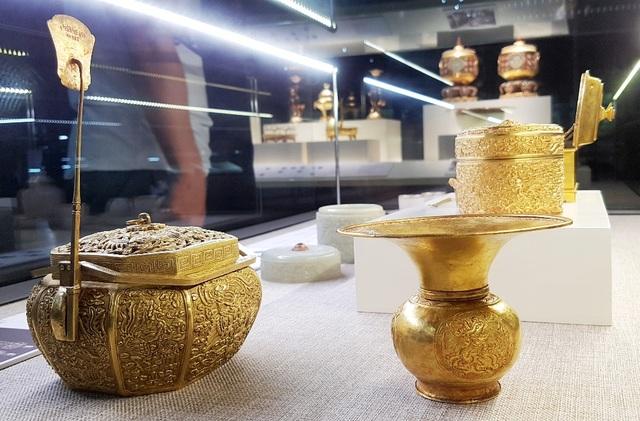 Từ trái qua là lồng ấp bằng vàng dùng bỏ than vào sưởi ấm mùa đông, ống nhổ bằng vàng dùng đựng nước thừa và nước cốt trầu và hộp vàng dùng để đựng trầu cau.