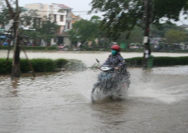 Người dân lái xe xông qua nước lũ