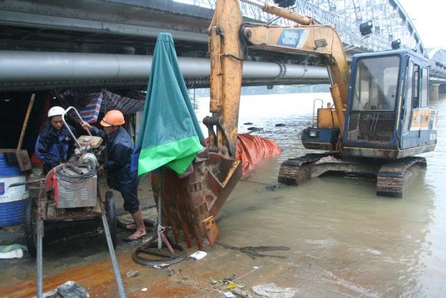 Các công nhân của Dự án cải thiện môi trường nước TP Huế di chuyển vật dụng dưới cầu Trường Tiền tránh lụt