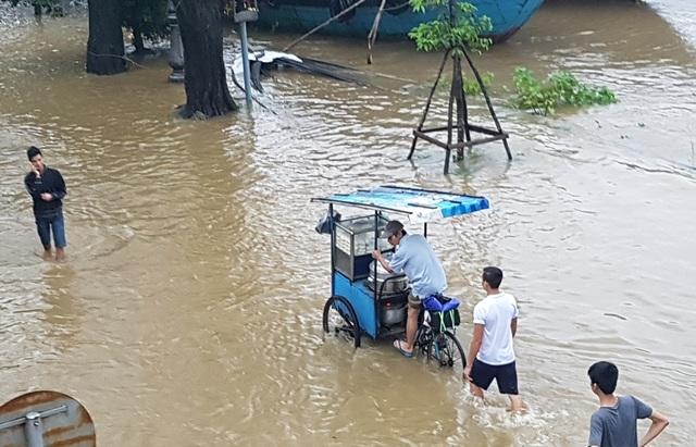 Xe bánh bao cố gắng vượt qua dòng nước lũ để đi bán mẻ bánh mới ra lò lúc chiều